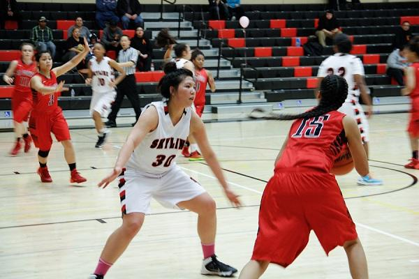 Trojans Janice Coronado (#30) blocking Las Positas Jasmine Rezonable (#15) while teammates struggle in the background.