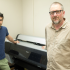 Professor Esfahani (left) in Professor Bridenbaugh's (right) office standing in front of a large format digital printer that will be used in the new digital media lab on May 13, 2014. Both Professors will be in charge of operating the new lab.