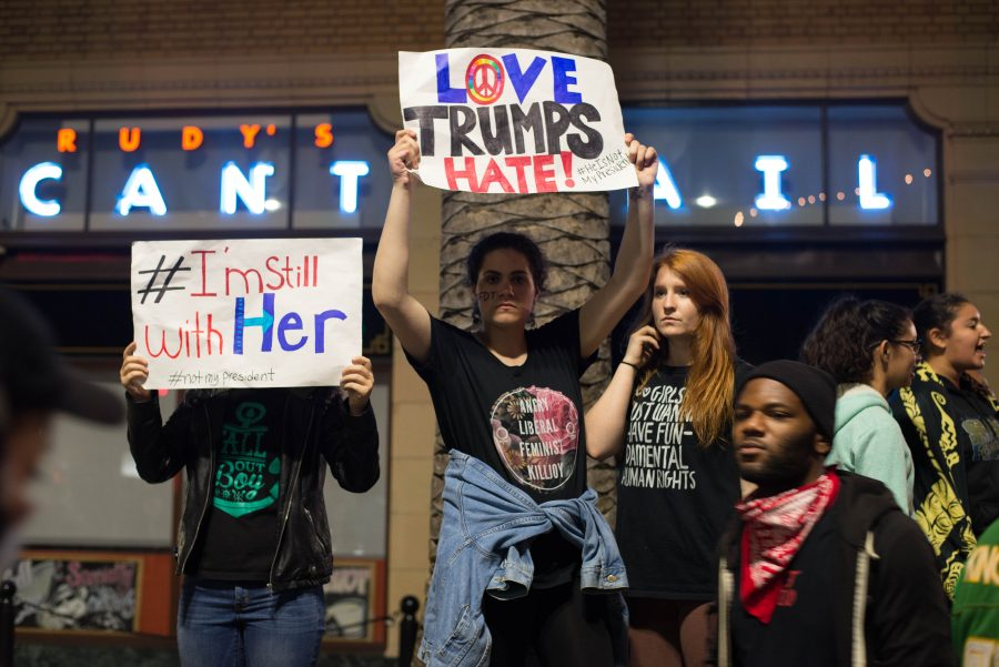 Protesters+hold+signs+denouncing+President-elect+Donald+Trump%E2%80%99s+campaign+on+Nov.+10%2C+2016+in+Oakland%2C+Calif.