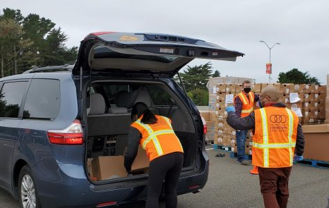 Volunteers load boxes of free groceries, each weighing about 39 pounds and valuing around $60, Wednesday, Sept. 2, 2020.
