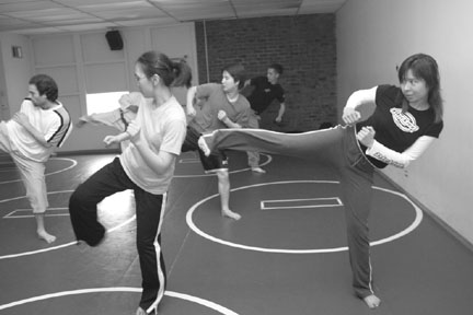 Jennifer Wong (right) practices side kicks with other students in her self defense class. Being able to defend yourself helps you feel safe and confident. This strength is not used to harm others, but only to protect yourself. (Bob Varner)