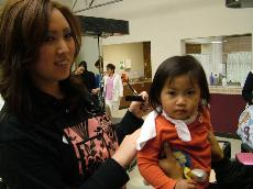 Michelle Wang (left) cuts her daughter's hair to helpe promote