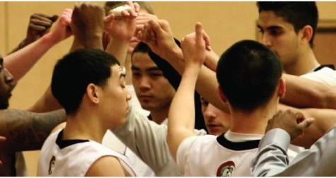 Last semester's men's basketball team huddle together during half-time.