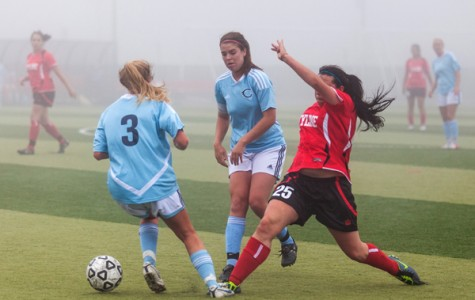 Forward Brooke Penner attempts to reach the ball behind two opponents.