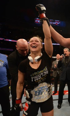 Rousey recieves her belt from UFC president Dana White after her win.