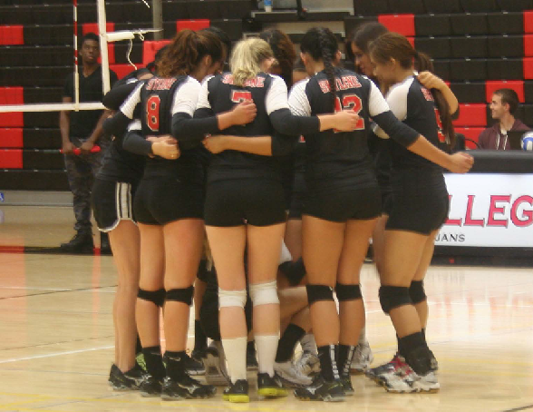 The Lady Trojans huddle after their victory.