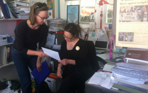 American Teacher Federation President, Alisa Messer, reviews paperwork with a collegue at City College of San Francisco