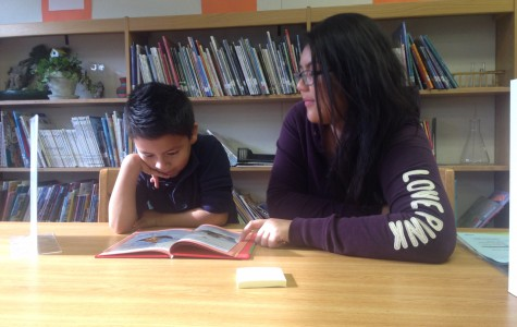3rd grader Joseph Dominguez, and tutor Mariden Totantes reading together.
