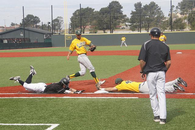 Skyline College Trojans' Phil Caulfield (#2) sliding towards first base, as Cañada College's Sean Walsh (#45) beats him to it. The game took place on March 14, 2015 between the Skyline College Trojans and Cañada College Colts.
