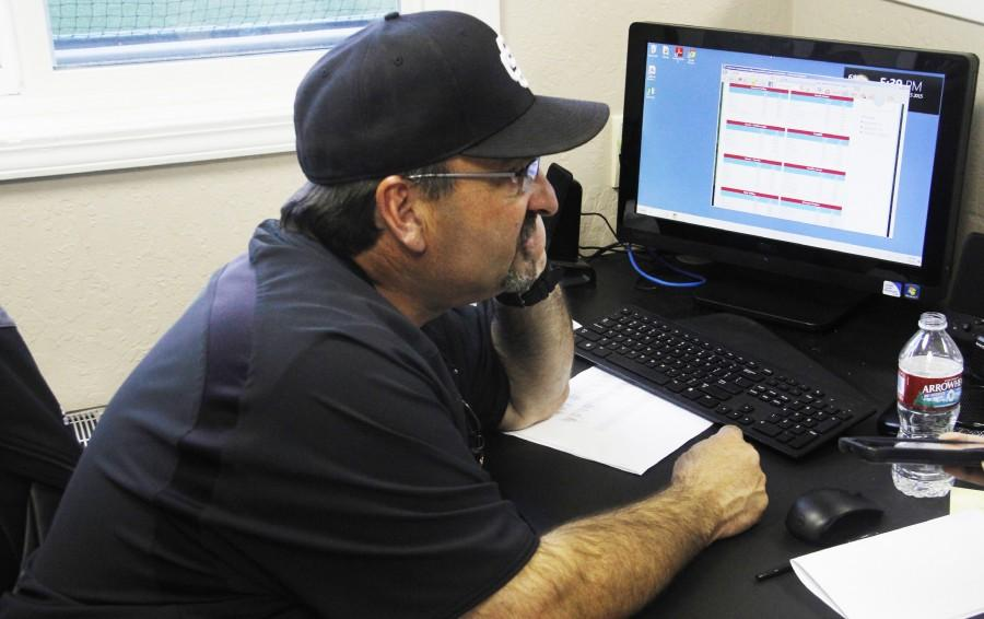 Skyline College Baseball Head Coach Dino Nomicos  looking up information on a computer at the campus baseball field booth after a game during the Spring 2015 semester.