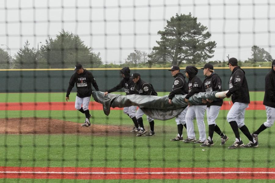 The Skyline Trojans brings in a tarp to cover the pitcher's mound during the game at Skyline College on March 12, 2016.