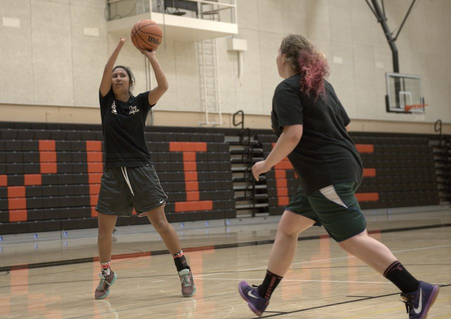 Ariana Sheehy (left) taking a shot at the basket during practice.