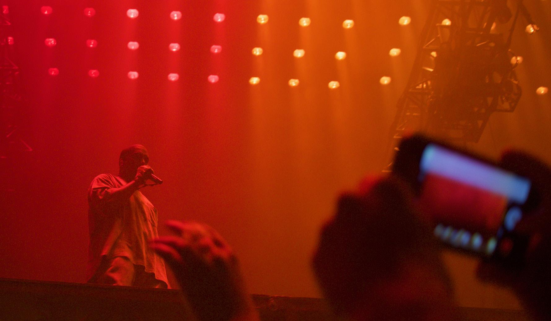 West raps high above the crowd in an unadorned, but intimate concert.