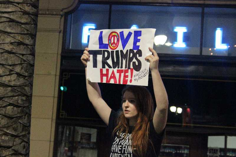 Anti-trump+protestor+holds+up+a+sign+that+reads+%E2%80%9Clove+trumps+hate%E2%80%9D+following+hashtag%2C+%E2%80%9C%23notmypresident%E2%80%9D+on%0D%0ANov.+10%2C+2016+at+19th+street+to+31st+street%2C+in+Oakland%2C+Calif.