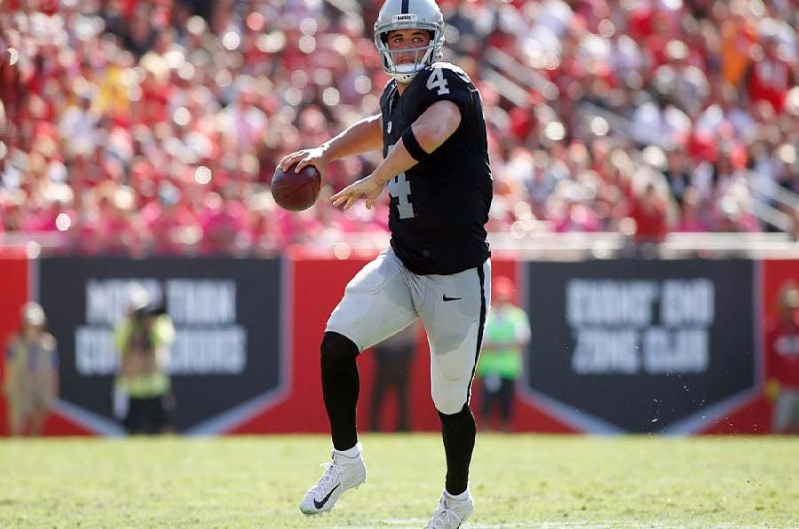 Quarterback+Derek+Carr+%234+of+the+Oakland+Raiders+looks+for+an+open+receiver+during+the+fourth+quarter.