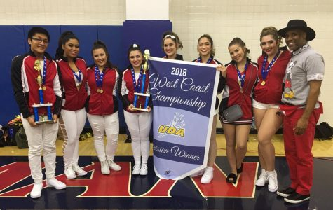 The Skyline College dance team holding their team's 2018 West Coast Championship banner and individual awards.