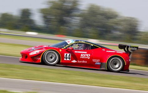 A red racing car is seen here on a race track during daytime.
